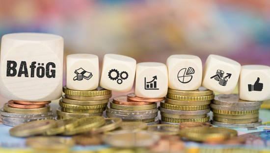"""Verschiedene Würfel, auf dem größten ganz links steht """"BAföG"""", auf den kleineren sind diverse Symbole (Daumen hoch, Balken- und Kuchendiagramme, Geld)"""