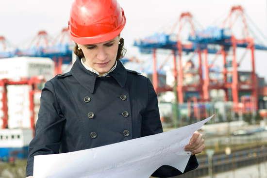 Bauingenieurin schaut auf Bauzeichnung, im Hintergrund Hafen (Kräne)