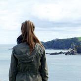 Junge Frau schaut von Steilküste aufs Meer