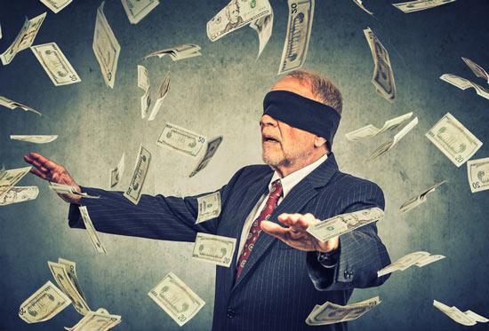 Mann im Anzug mit verbundenen Augen steht im Geldscheinregen