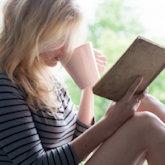 Frau sitzt auf Fensterbank, liest ein altes Buch und trinkt einen Cappuccino