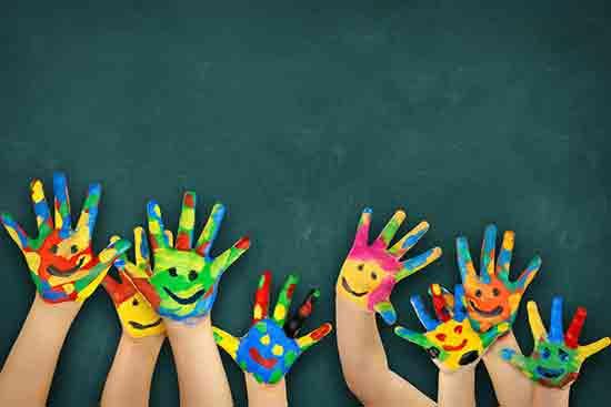 Bunte Kinderhände vor einer Tafel
