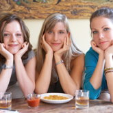 Drei Mädels sitzen auf einer Couch, Kinn auf die Arme gestützt