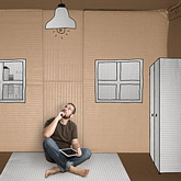 Mann sitzt in Wohnung (aus Karton) und überlegt, wie er sein neues Zimmer einrichten soll.