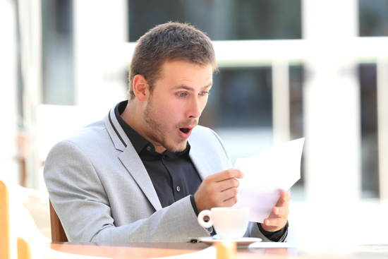 Mann liest etwas in einem Café und scheint erstaunt