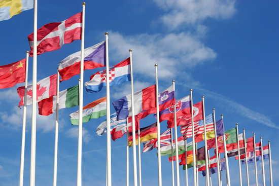 Flaggen von vielen Ländern der Welt (u.a. Deutschland, USA, China, Dänemark, Frankreich, Portugal, Großbritannien flattern im Wind