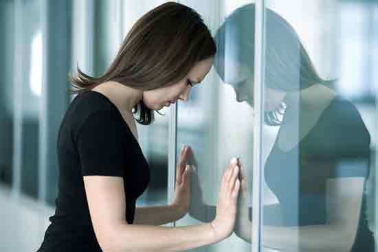 Junge Frau lehnt mit ihrem Kopf an einer Glasscheibe