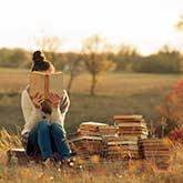Junge Frau sitzt ein Buch lesend auf einer Wiese