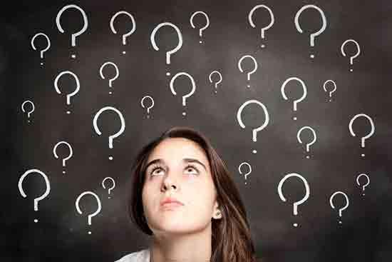 Studieninteressierte sitz vor einer Tafel mit Fragezeichen
