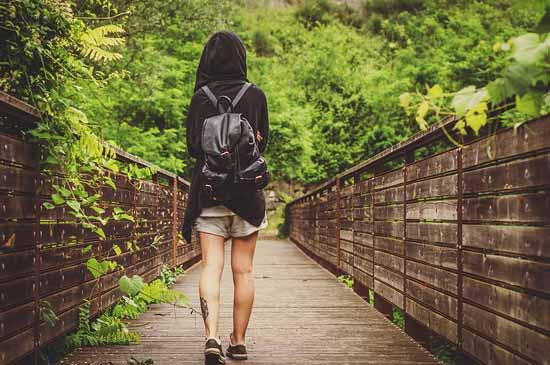 Frau läuft auf einer Brücke auf einen Wald zu