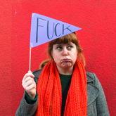 """Junge Frau vor rotem Hintergrund hält ein Wimpel mit Aufschrift """"Fuck"""" hoch."""