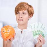 Nachdenkliche Frau mit Sparschwein und Geldscheinen in der Hand