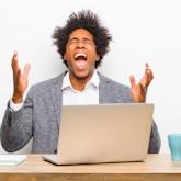 """Junger Mann am Computer, schreit und hebt Arme hoch: """"Warum ich?"""""""