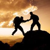 Zwei Bergsteiger im Gegenlicht, der auf dem Gipfel hilft dem anderen hoch