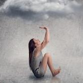 Frau sitzt unter einer Wolke, die regnet.
