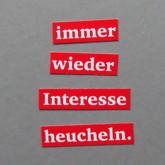 """Ausgeschnitte Worte (weiß auf rot) auf grauem Hintergrund: """"immer wieder Interesse heucheln."""""""