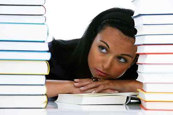 Studentin schaut ratlos zwischen Büchern hervor