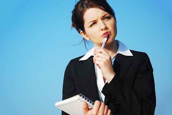 Eine junge Frau mit Stift und Block in der Hand überlegt