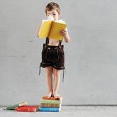 Junge mit Lederhose steht auf einem Stapel Bücher und liest ein Buch