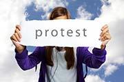 Junge Frau hält Schild mit Protest in der Hand