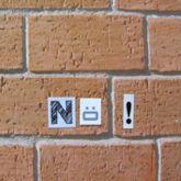 """Nö!"" auf Zetteln an Backsteinwand geklebt"