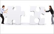 2 Personen schieben menschengroße Puzzleteile zusammen