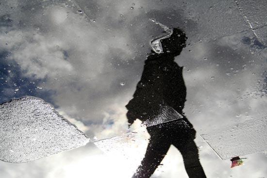 Spiegelung einer Person in einer Regenpfütze