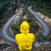 Person mit Regenjacke sitzt vor Kurve (und kann sich nicht entscheiden).