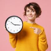 Frau in gelbem Pulli vor raus Hintergrund zeigt auf eine Uhr, deren Zeiger 9 Minuten vor drei stehen.