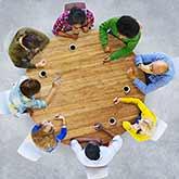 Runder Tisch mit Personen, die Stifte in der Hand haben, aber keine Blätter