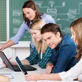 Drei Schüler arbeiten an Tablet/Laptop im Klassenzimmer und werden von Lehrerin beraten