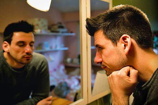 Mann schaut in den Spiegel –und entdeckt einen anderen Ausdruck.