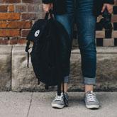 Person mit Rucksack vor Mauer