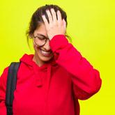Studentin lächelt und haut sich mit flacher Hand gegen die Stirn.