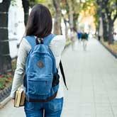Studentin von hinten läuft einen Weg lang