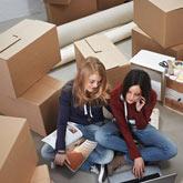 2 junge Frauen sitzen vor einem Laptop – im Hintergrund sind viele Umzugskisten