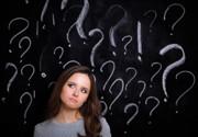 Frau vor einer Tafel mit Fragezeichen