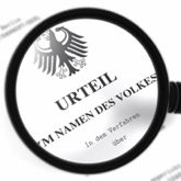 """Unscharfer Gesetzestext mit Lupe, in der man unter dem Staatswappen """"Urteil im Namen des Volkes"""" sehen kann"""