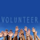 """Blauer Himmel mit """"Wolken"""", die das Wort """"Volunteer"""" bilden, am unteren Bildrand sieht man Hände in die Luft gestreckt"""