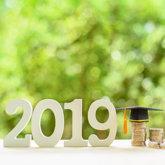 2019 aus Holz, kleiner Doktorhut, Geldmünzen, Hintergrund grün verschwommen