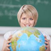 Blonde Frau mit einem Globus in der Hand vor dem Hintergrund einer Tafel
