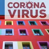 Buntes Wohnhaus mit Schriftzug Corona Virus (Montage)