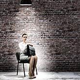 Bewerberin sitzt auf einem Stuhl unter einer Lampe vor einer Backsteinwand