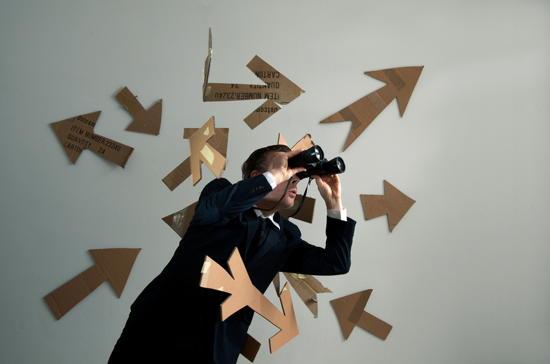 Mann schaut durch Fernglas; umgeben von Pfeilen in verschiedene Richtungen