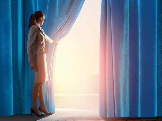 Frau hinter dem Vorhang auf einer Bühne