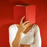 Frau liest rotes Buch (dadurch Gesicht verdeckt)