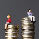 Zwei Münzstapel, auf dem niedrigeren sitzt eine Frauenfigur, auf dem höheren eine Männerfigur