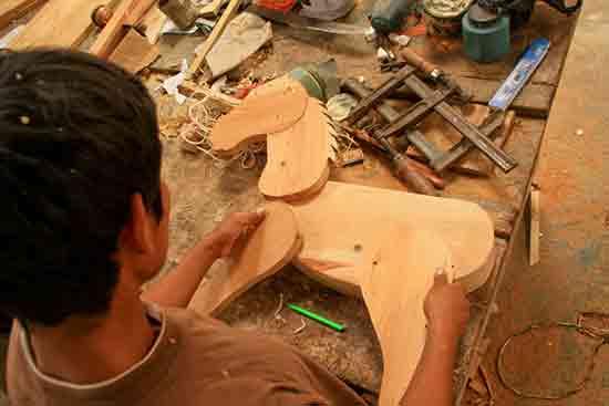 Ein Junge aus einem Entwicklungsland baut ein Holzpferd