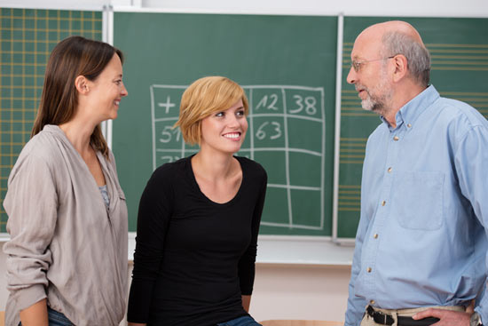 Junge Lehrerin mit Kollegen im Gespräch in der Klasse vor Tafel