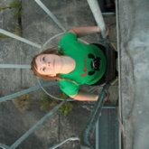 Frau auf Leiter, schaut nach oben, von oben fotografiert